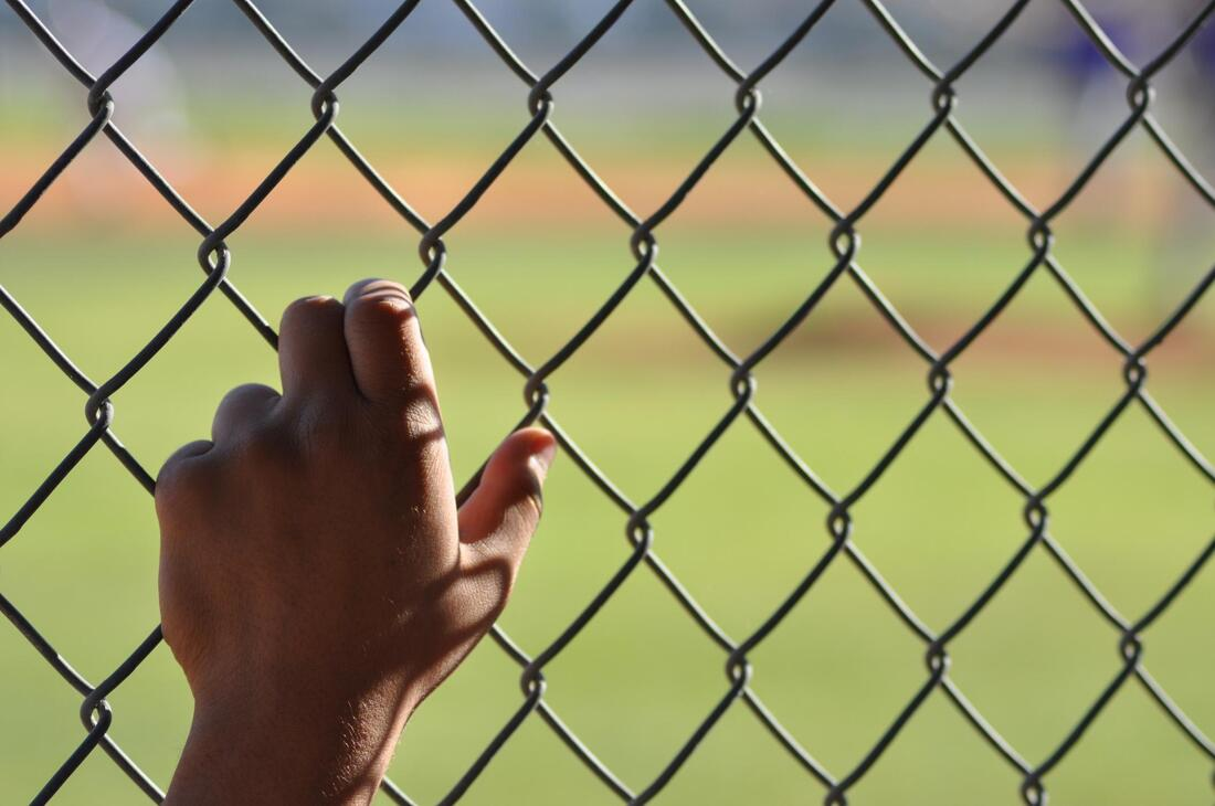 man holding chain link fences