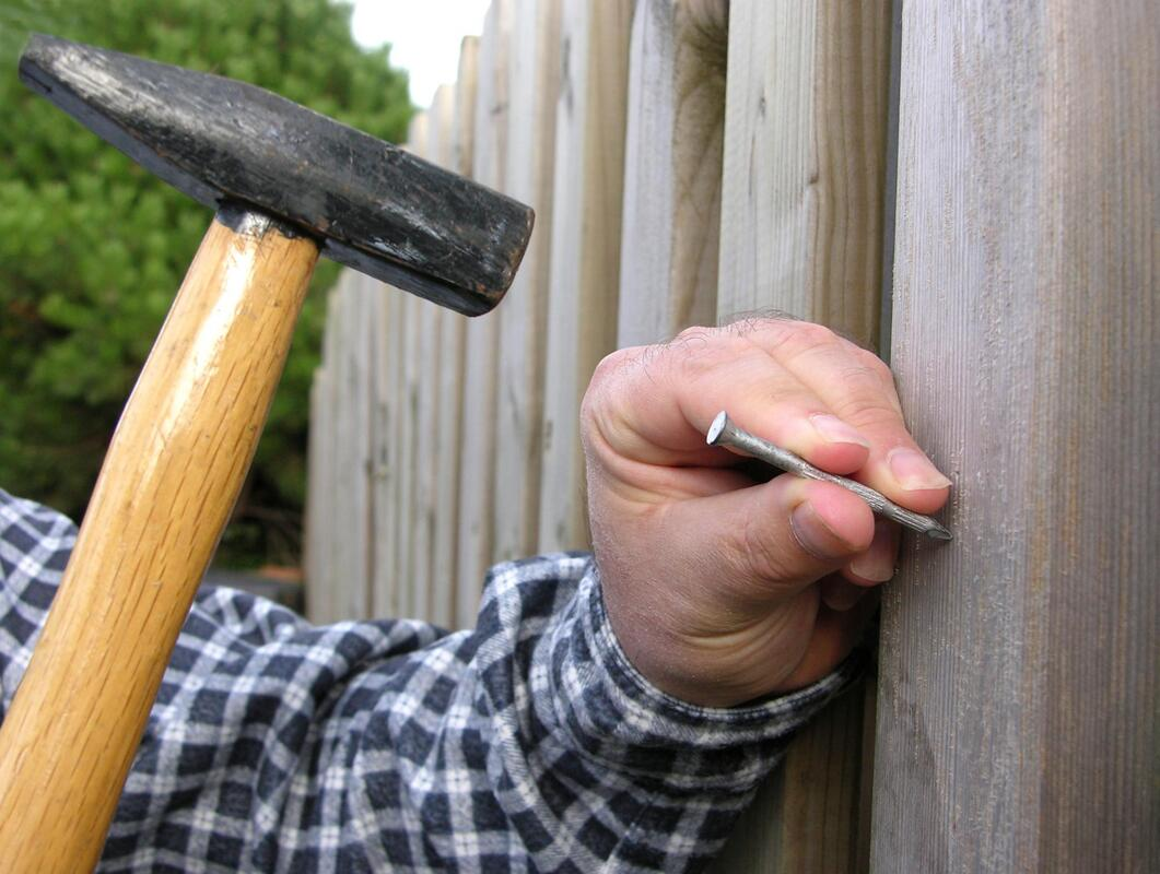 professional fencing worker working on fence repair